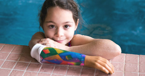 A child amputee wearing her water arm in a swimming pool.