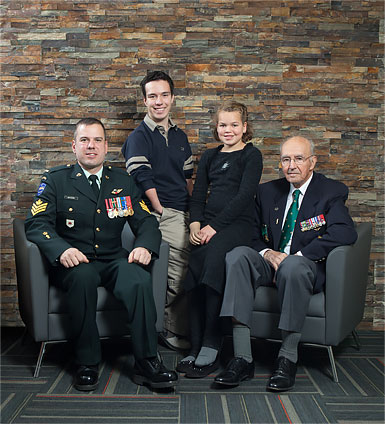 Two war amputee veterans posing with two young child amputees.