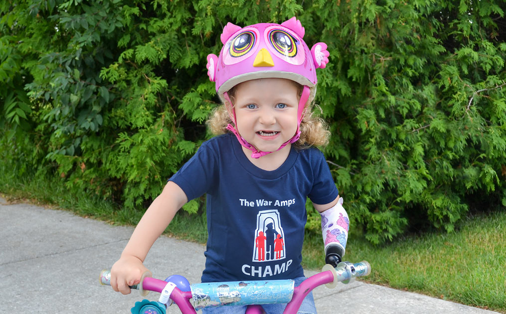 Michaela using her artificial arm with a bike attachment to ride her bike. See Michaela's story.
