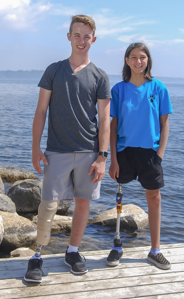 Safety Ambassadors Rebecca and Adam, both leg amputees, standing on a dock by a lake.