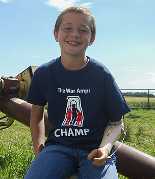 Champ Ernie, an arm amputee, posing in front of a grain auger.