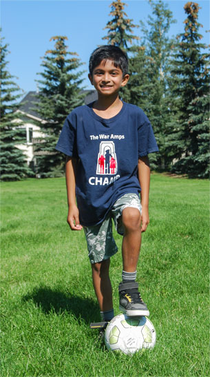 Champ Jordan standing in a field with his foot resting on top of a soccer ball.